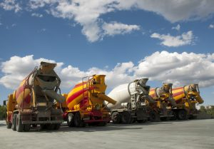 Five Concrete Mixing Trucks with a blue sky