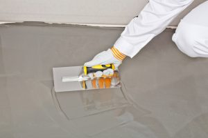 Worker finishing and smoothing a concrete floor
